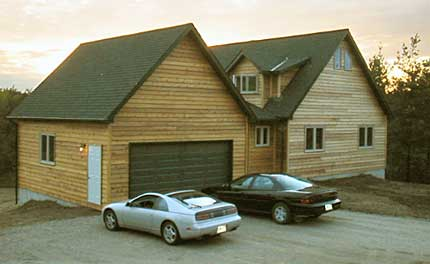 Image of the rear exterior of the model C-510 chalet design showing garage, doors and back of the house.