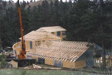 Picture of large home being framed. All plans packages include layout of the roof framing details and materials, including suggested engineering.